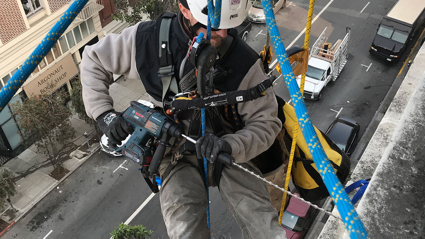 Rope access technician driving a Helifix pin